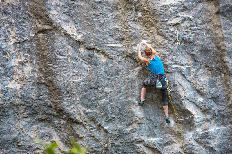 La muchacha sube la roca imagen de archivo libre de regalías