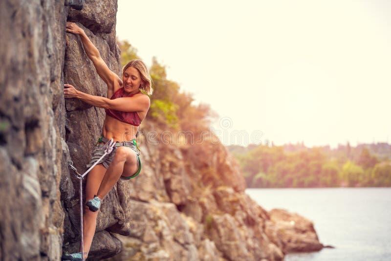 La muchacha sube la roca imagen de archivo