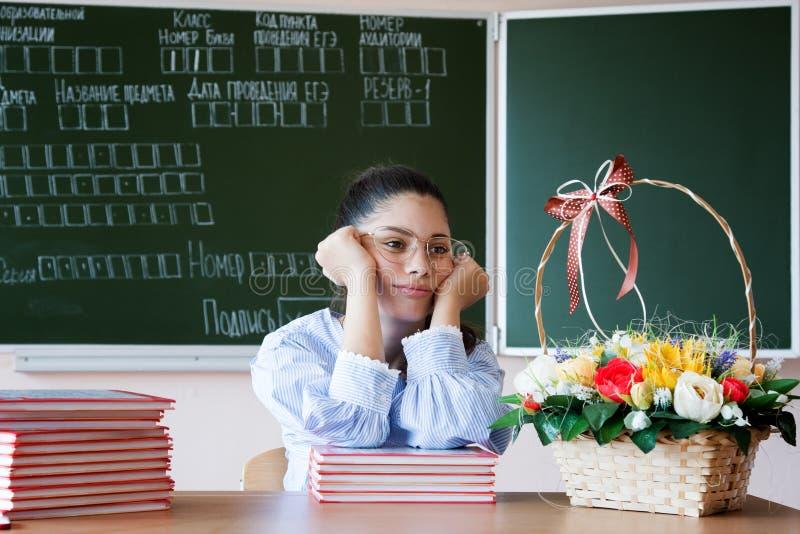 La muchacha subrayada en vidrios se sienta contra la pizarra en sala de clase fotos de archivo libres de regalías