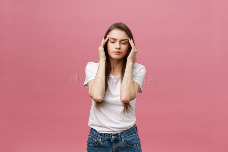 La muchacha sufre de dolores de cabeza terribles y comprime la cabeza con los fingeres Olvide y recuerde algo, sufra de imágenes de archivo libres de regalías