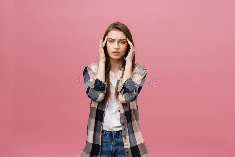La muchacha sufre de dolores de cabeza terribles y comprime la cabeza con los fingeres Olvide y recuerde algo, sufra de fotografía de archivo