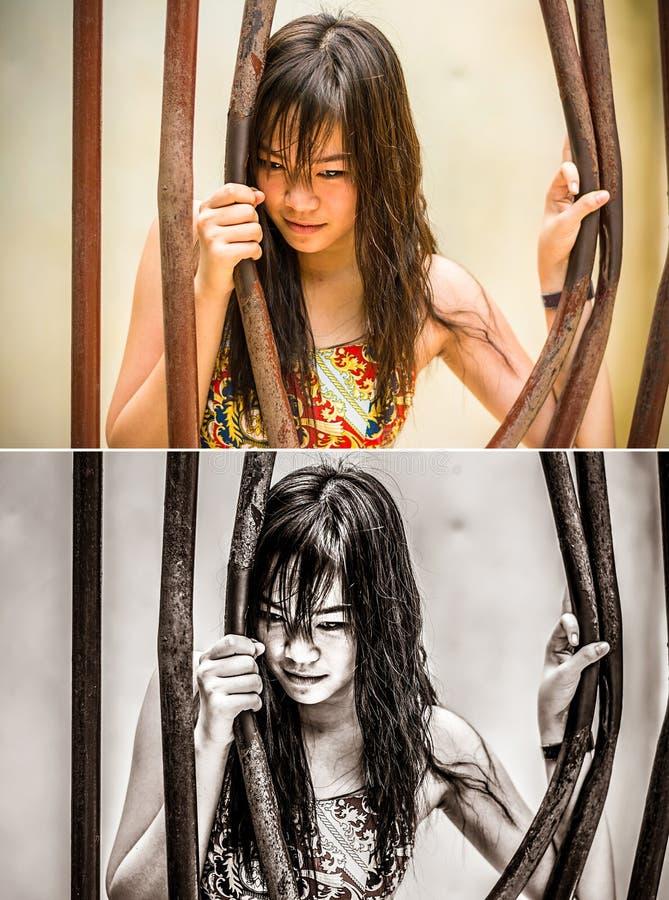 La muchacha tailandesa asiática está doblando la barra de la prisión con su poder en grun imagen de archivo libre de regalías