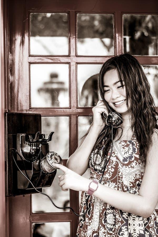 La muchacha tailandesa está hablando con un teléfono de la viejo-moda en negro y pizca fotografía de archivo libre de regalías