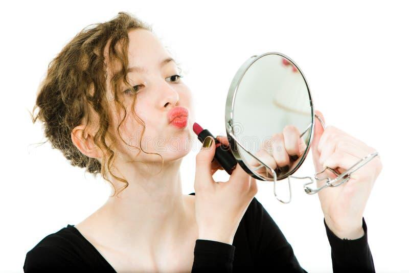 La muchacha Teenaged en la fabricación negra del vestido compone en el espejo redondo - barra de labios imagenes de archivo