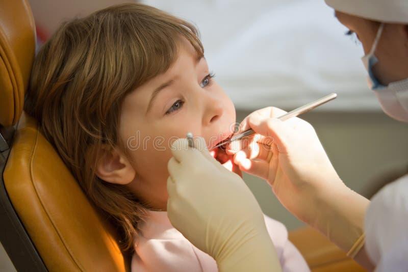 La muchacha tiene diente periódico de la encuesta en oficina médica fotografía de archivo libre de regalías