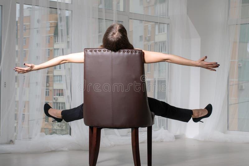 La muchacha tiene un resto que se sienta en una silla imágenes de archivo libres de regalías