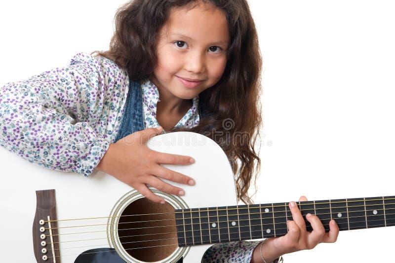 La muchacha toca la guitarra foto de archivo