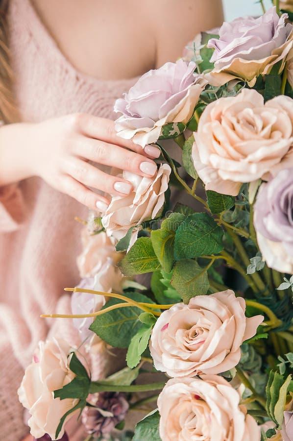La muchacha toca la rama floreciente con la mano Rosas en casa Floración de la primavera de la sensualidad Toque la delicadeza de fotos de archivo