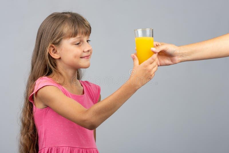 La muchacha toma de su mano un vidrio de zumo de naranja foto de archivo libre de regalías