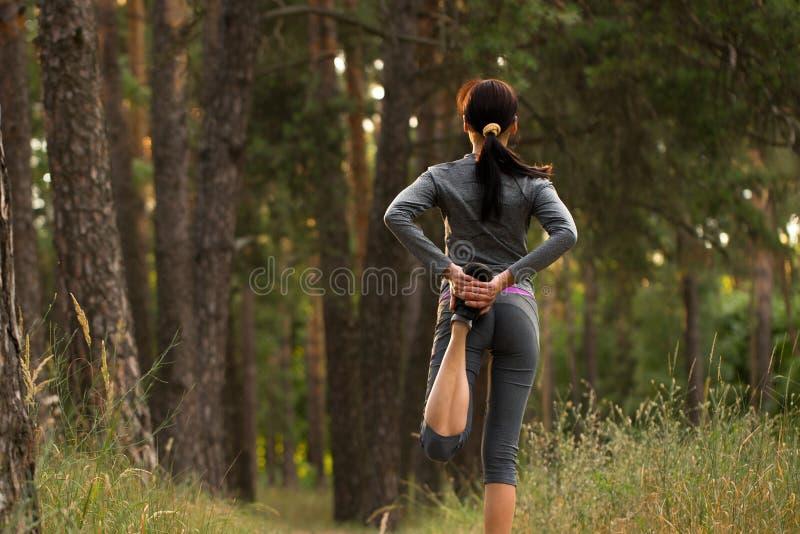 La muchacha toma deportes en naturaleza foto de archivo