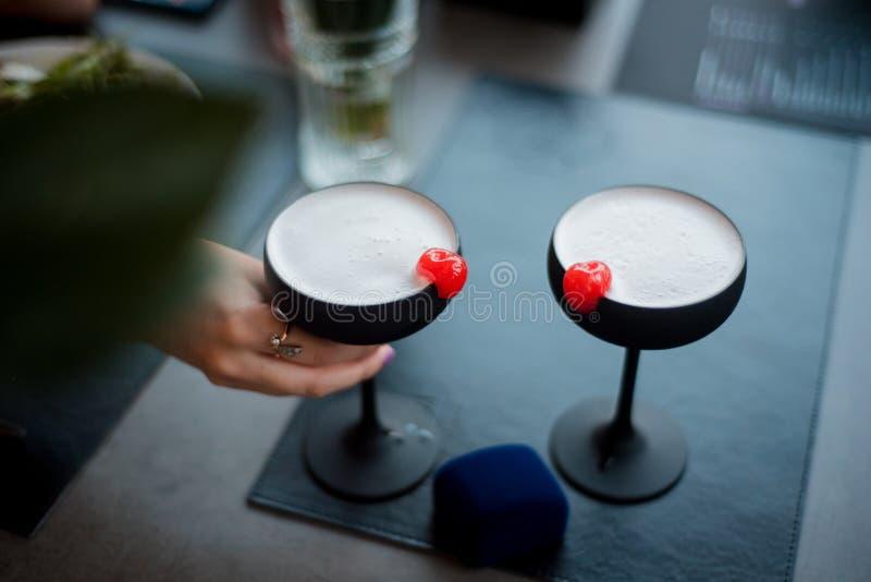 La muchacha toma un vidrio negro con un cóctel Bebida espirituosa con la cereza Mano en el fondo de una servilleta y de una a imagen de archivo libre de regalías