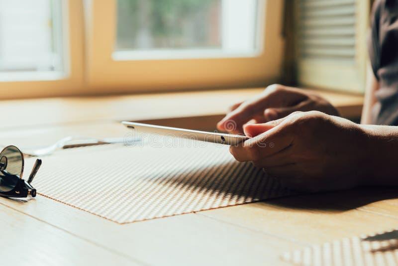 La muchacha trabaja en la tableta fotos de archivo