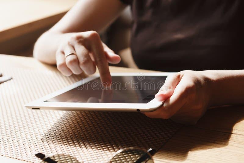 La muchacha trabaja en la tableta foto de archivo libre de regalías