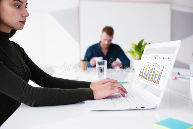La muchacha trabaja en un ordenador portátil con estadísticas de la compañía Concepto de distribución y de interconexión de Inter fotos de archivo