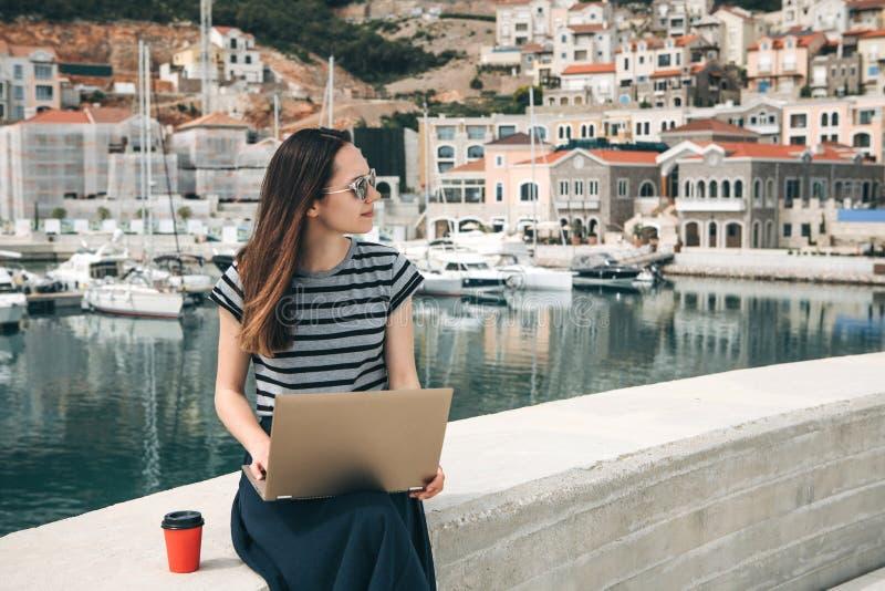 La muchacha trabaja en un ordenador port?til fotografía de archivo