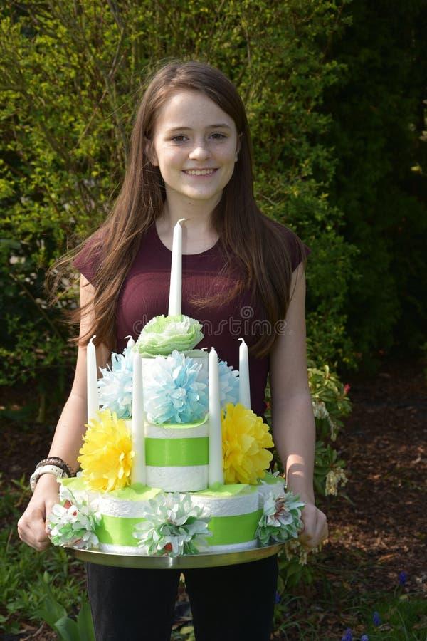 La muchacha trae la torta de cumpleaños hecha del papel higiénico imagen de archivo libre de regalías