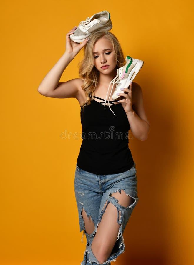 La muchacha trastornada joven sostiene viejos pares de zapatos sucios en su cabeza Feels frustrada y desesperada foto de archivo