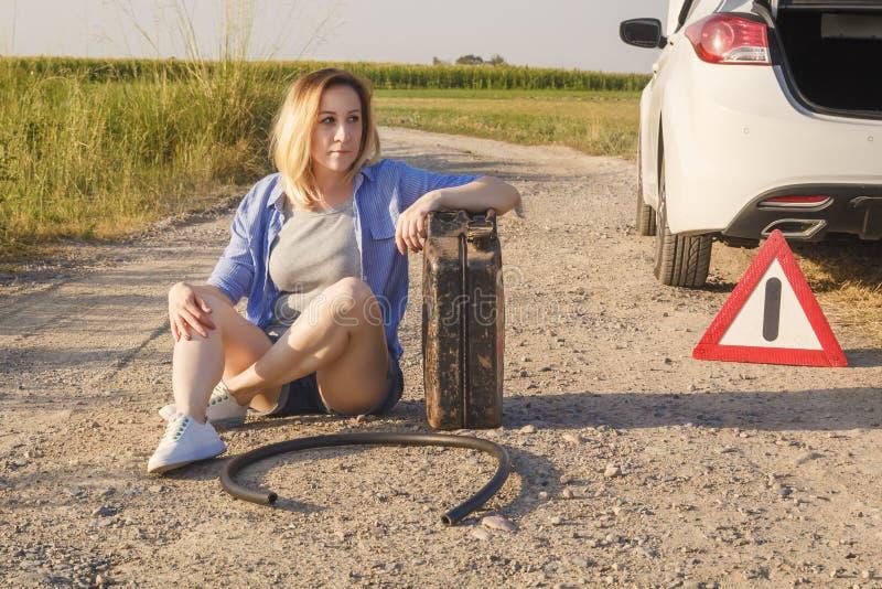 La muchacha triste cuyo conductor ha corrido de la gasolina en un coche en un camino rural sienta para ayuda que espera con un bo fotos de archivo