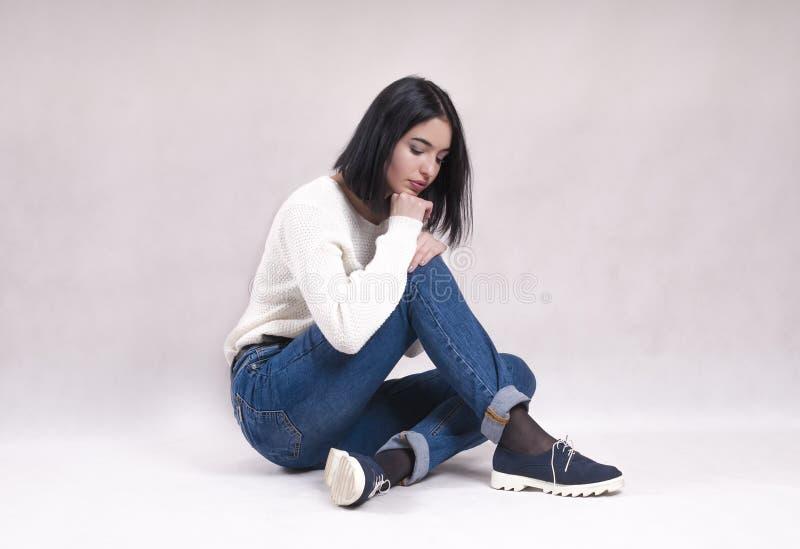 La muchacha triste se sienta en el piso en dificultades de la depresión de las noticias de los vaqueros fotografía de archivo