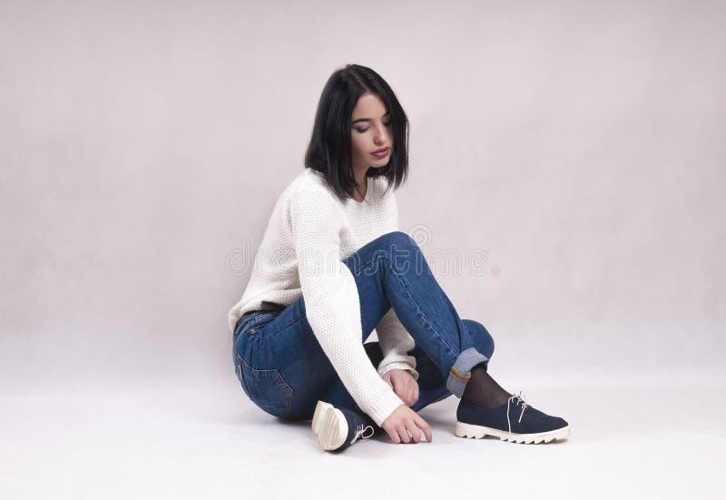La muchacha triste se sienta en el piso en dificultades de la soledad de la depresión de las noticias de la soledad de los vaquer fotos de archivo libres de regalías