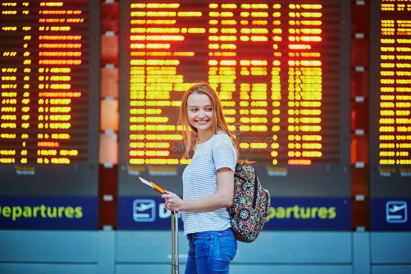La muchacha turística con la mochila y continúa el equipaje en aeropuerto internacional, cerca de tablero de la información del v imagen de archivo libre de regalías