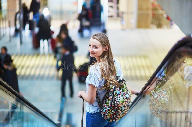 La muchacha turística con la mochila y continúa el equipaje en aeropuerto internacional, en la escalera móvil fotografía de archivo