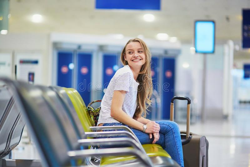 La muchacha turística con la mochila y continúa el equipaje en el aeropuerto internacional, esperando vuelo fotografía de archivo