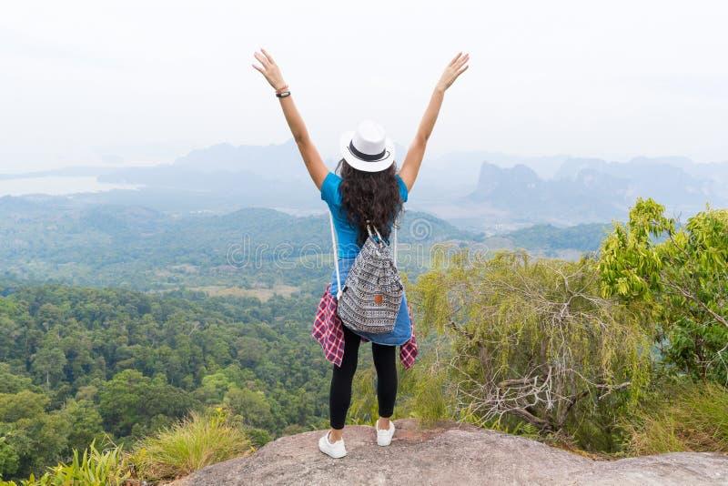 La muchacha turística con la mochila que se coloca en de la montaña de los devolver vista posterior aumentada superior disfruta d imagen de archivo