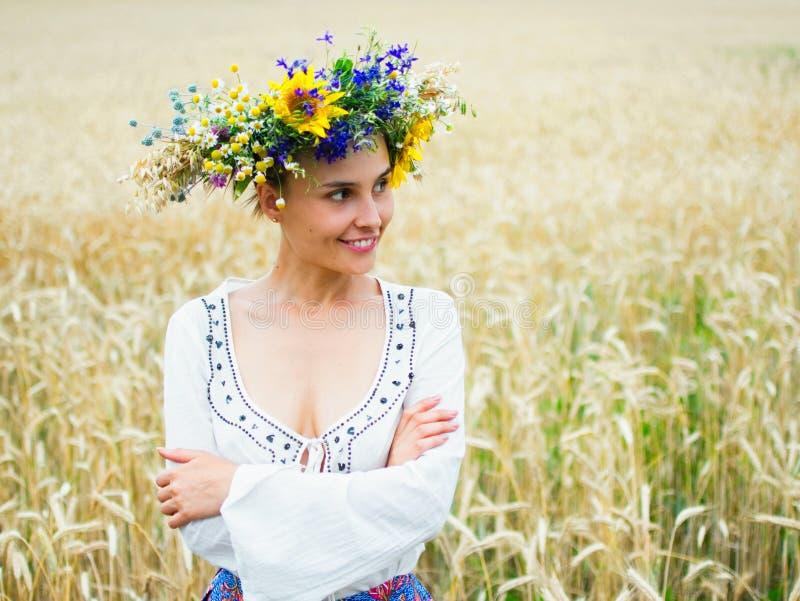 La muchacha ucraniana en una guirnalda hermosa camina a través del prado del verano Visten a la muchacha en ropa étnica con fotografía de archivo libre de regalías