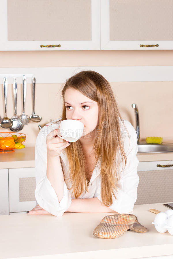 La muchacha una camisa de los hombres blancos con el pelo que fluye largo está bebiendo codos de la cocina del té en la tabla Mañ imagenes de archivo
