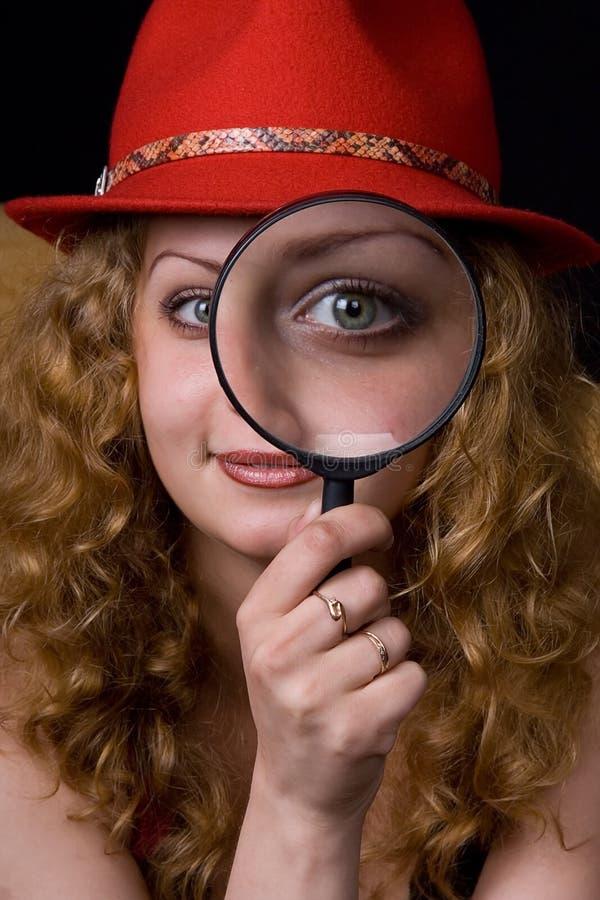 La muchacha una lupa un sombrero imagenes de archivo