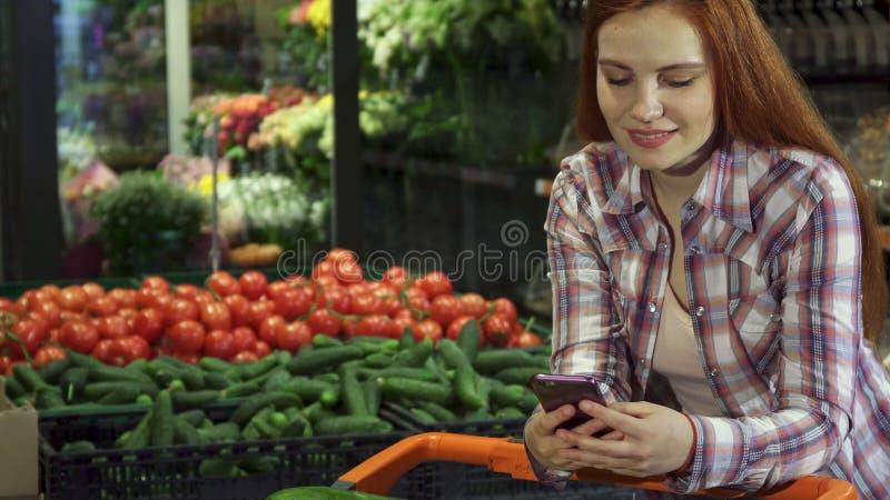 La muchacha utiliza smartphone en el hipermercado fotos de archivo libres de regalías