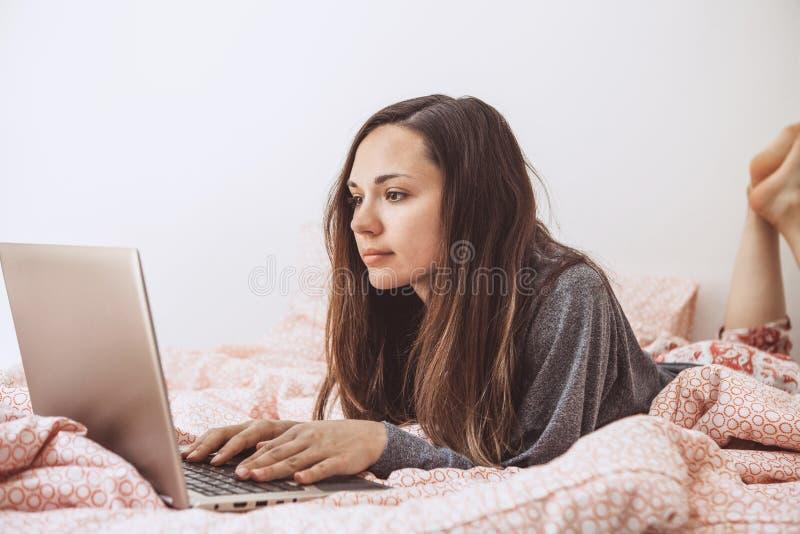 La muchacha utiliza un ordenador port?til imágenes de archivo libres de regalías