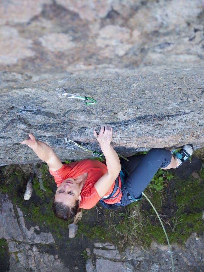 La muchacha valiente sube para arriba el acantilado fotografía de archivo libre de regalías