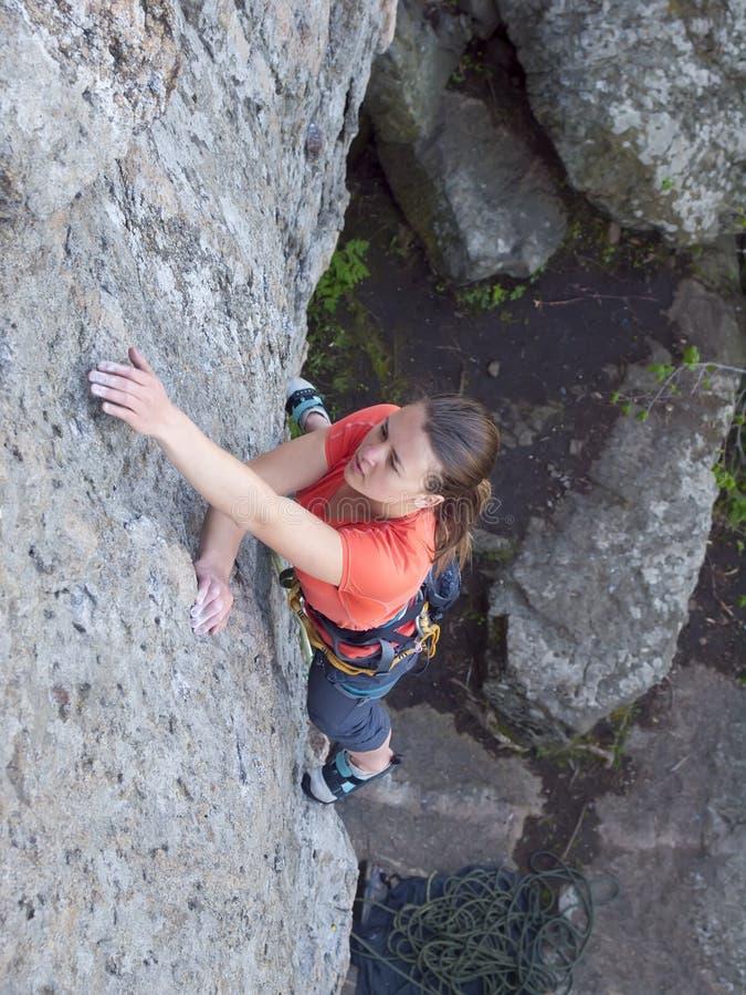 La muchacha valiente sube para arriba en las rocas peligrosas fotografía de archivo