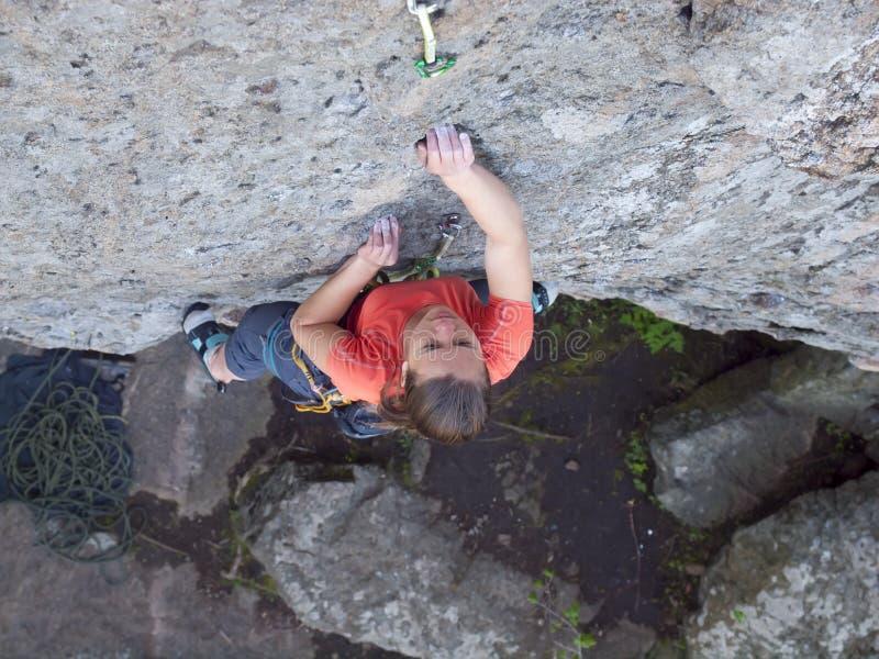 La muchacha valiente sube para arriba en las rocas peligrosas imagen de archivo libre de regalías
