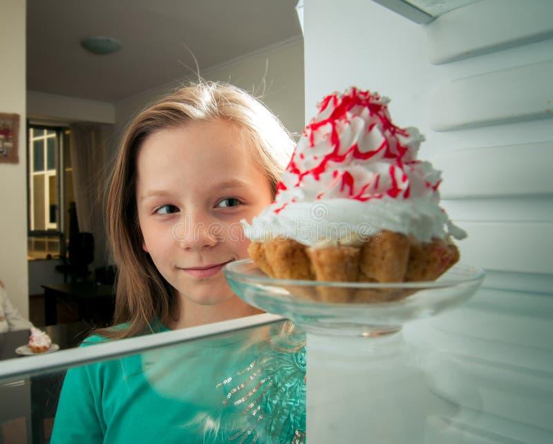 La muchacha ve la torta dulce imagen de archivo