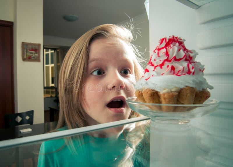 La muchacha ve la torta dulce el refrigerador imagenes de archivo