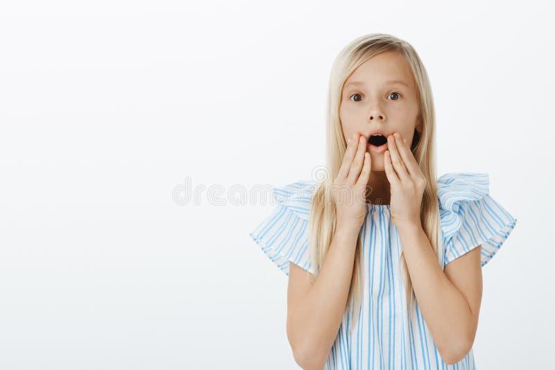 La muchacha ve la muñeca adorable en la tienda, pidiendo que la madre la compre Retrato de la hija de pelo rubio linda sorprenden imágenes de archivo libres de regalías