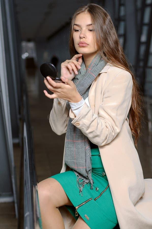 La muchacha ve su cara en un maquillaje del bolsillo imagen de archivo libre de regalías