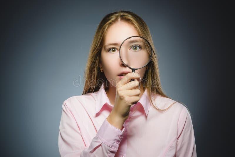 La muchacha ve a través la lupa, ojo del niño que mira con la lente de la lupa sobre gris imagen de archivo libre de regalías