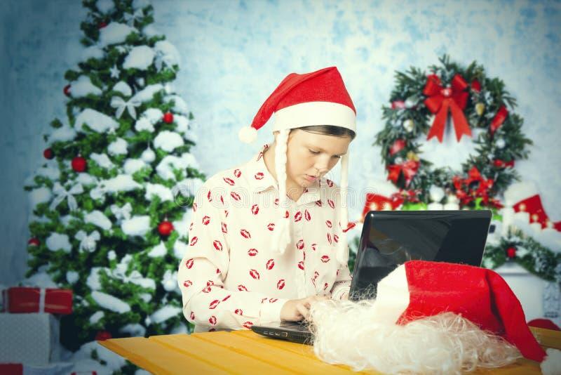 La muchacha vestida como Santa Claus se familiariza con en Internet imágenes de archivo libres de regalías