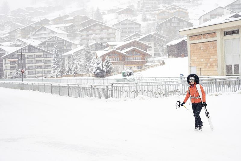 La muchacha vestida en la chaqueta roja, casco glassed y blanco del esquí del espejo, lleva los esquís en su hombro imagen de archivo libre de regalías