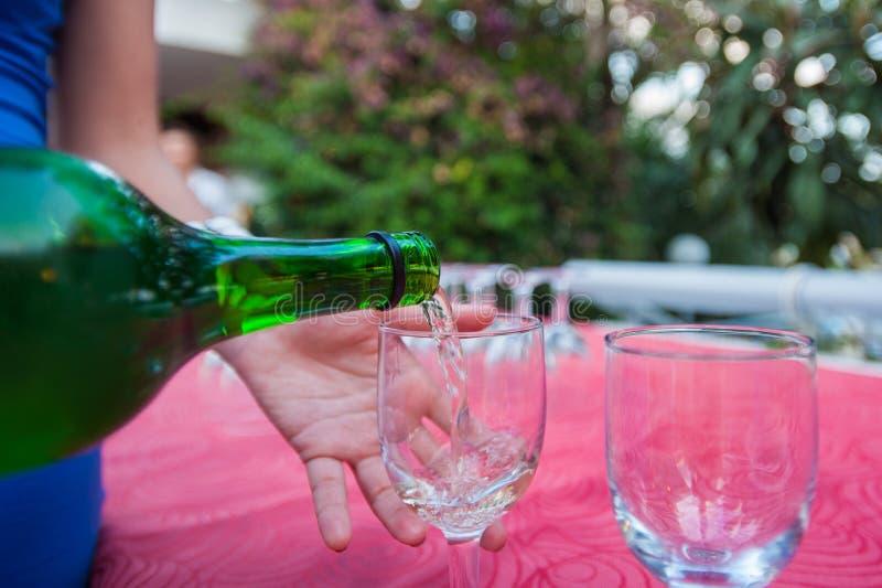 La muchacha vierte una copa de vino resto y alcohol foto de archivo