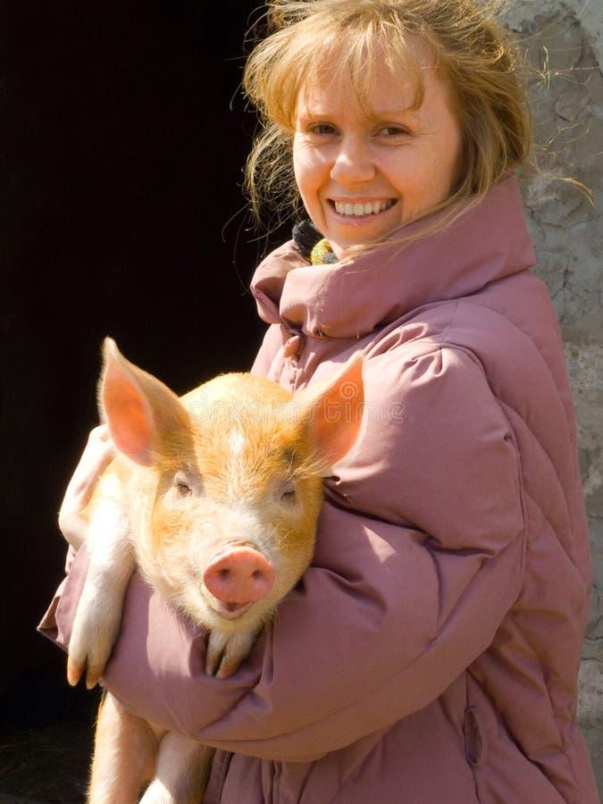 La muchacha y el cerdo fotografía de archivo