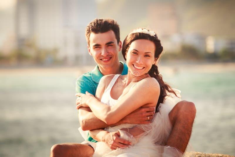 la muchacha y el individuo abrazan en piedra contra el mar imágenes de archivo libres de regalías