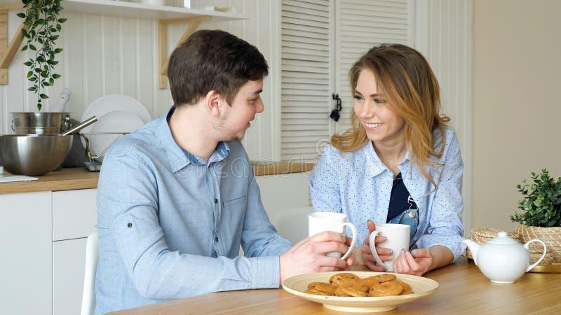 La muchacha y el individuo rubios tienen t? de consumici?n del desayuno en cocina fotografía de archivo libre de regalías