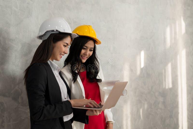 La muchacha y el ingeniero del negocio con la gente asiática trabajan con el ordenador portátil AR fotos de archivo libres de regalías