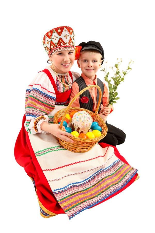 La muchacha y el muchacho con los huevos de Pascua y un d?a de fiesta se apelmazan imagen de archivo