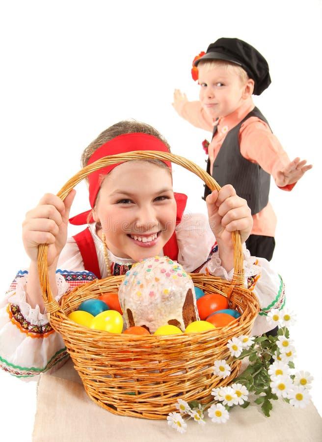 La muchacha y el muchacho con los huevos de Pascua y un d?a de fiesta se apelmazan foto de archivo